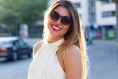 Módní portrét smějící se roztomilé mladé ženy na ulici