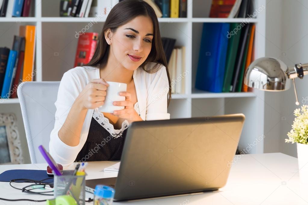 jolie jeune femme qui travaille avec l 39 ordinateur portable dans son bureau photo 91456814. Black Bedroom Furniture Sets. Home Design Ideas