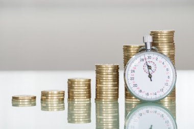 Stopwatch And Stacked Coins