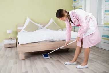 Housekeeper Cleaning Floor With Mop