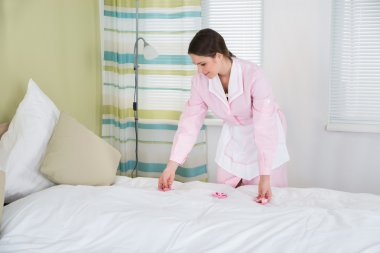 Housekeeper Decorating Bed With Flowers