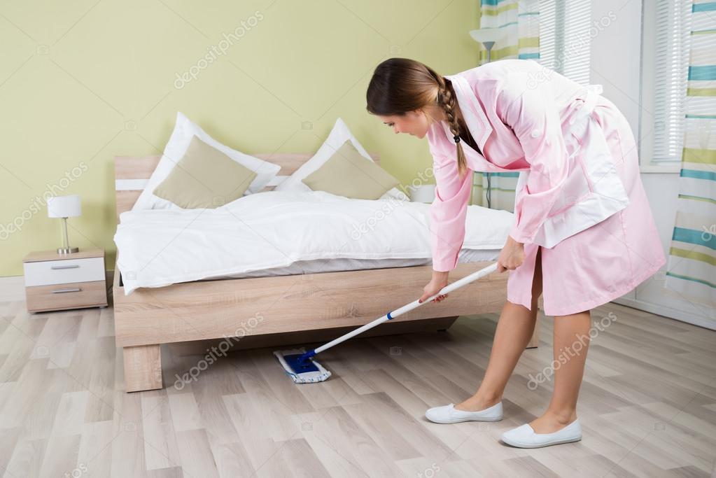 Ama de casa limpieza de piso con un trapeador foto de Baja empleada de hogar