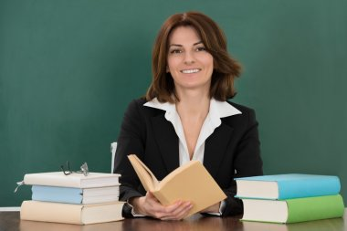 Female Teacher Sitting At Desk