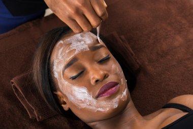 African Woman Applying Facial Mask