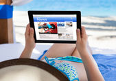 Woman Reading News At Beach