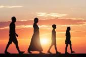 Famiglia che cammina contro il cielo drammatico