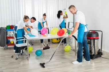 Janitors Cleaning Office After Party