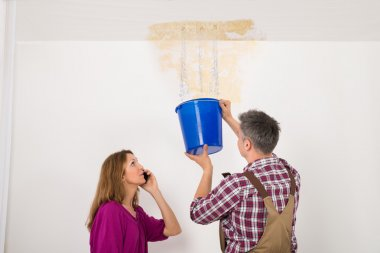 Worker Collecting Water In Bucket From Ceiling