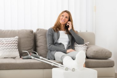 Woman With Plastered Leg Talking On Mobile Phone