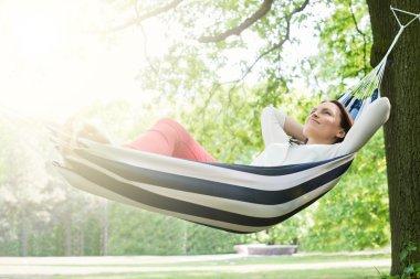 Young Happy Woman Relaxing In Hammock At Garden stock vector