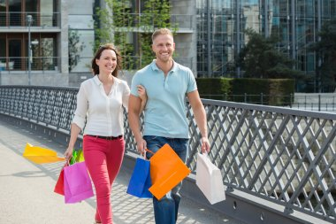 Couple Walking On Bridge With Shopping Bags