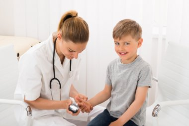 Doctor Examining Blood Sugar Of Little Boy
