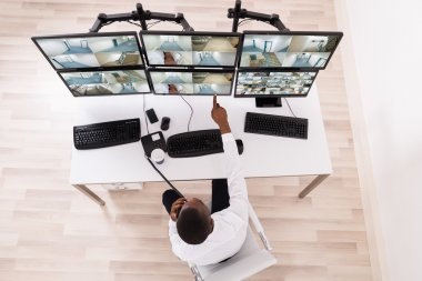 Male Operator Pointing At CCTV Footage On Computer