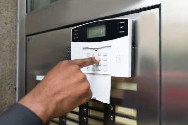 Businessperson Entering Code In Security System