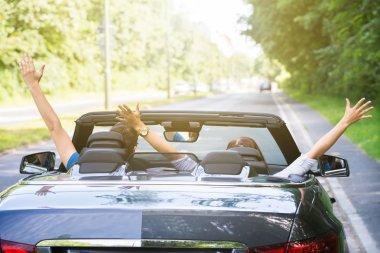 Couple Sitting In A Car Raising Their Arms