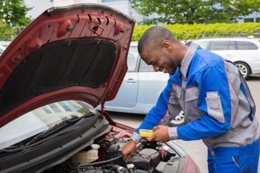 Mechanic Using Multimeter To Check Car Battery