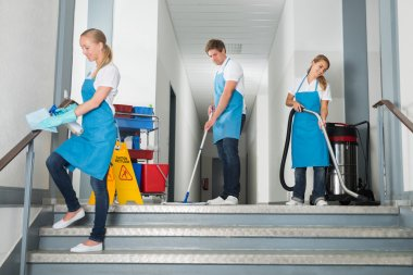 Janitors Cleaning Corridor With Cleaning Equipments