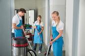 Skupina z domovníků čištění podlahy v chodbě