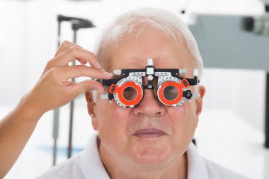Close-up Of An Optometrist Checking Senior Male Patient Vision With Trial Frame At Eye Clinic stock vector