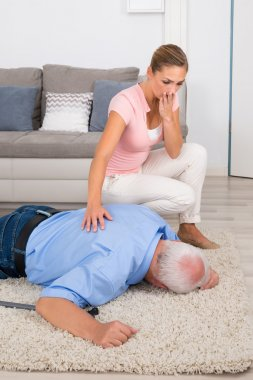 Woman Looking At Her Fainted Disabled Father
