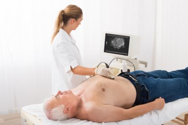 Doctor Using Ultrasound Scan On Abdomen Of Male Patient