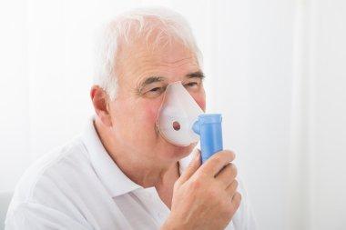Man Inhaling Through Oxygen Mask