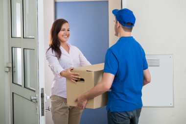 Woman Receiving Package From Delivery Man
