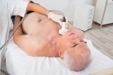 Man Getting Ultrasound Scan On Neck By Doctor