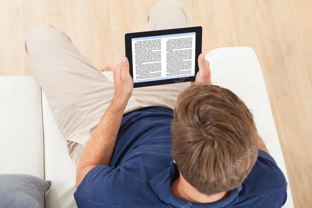 High angle view of man reading eBook while relaxing on sofa at home