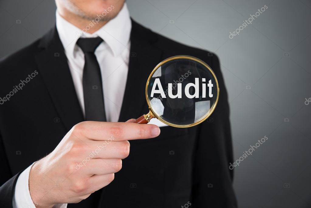 Businessman Showing Audit Word Through Magnifying Glass