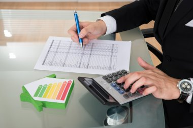 Businessman Calculating Energy Efficiency Rate