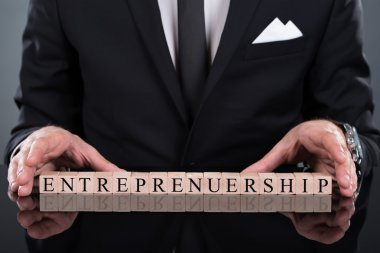 Businessman Showing Entrepreneurship Blocks