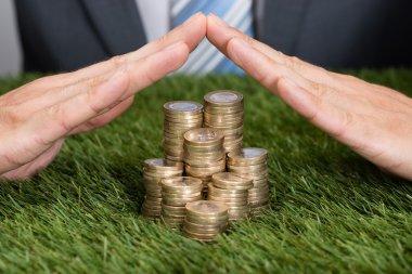 Businessman Shielding  Coins