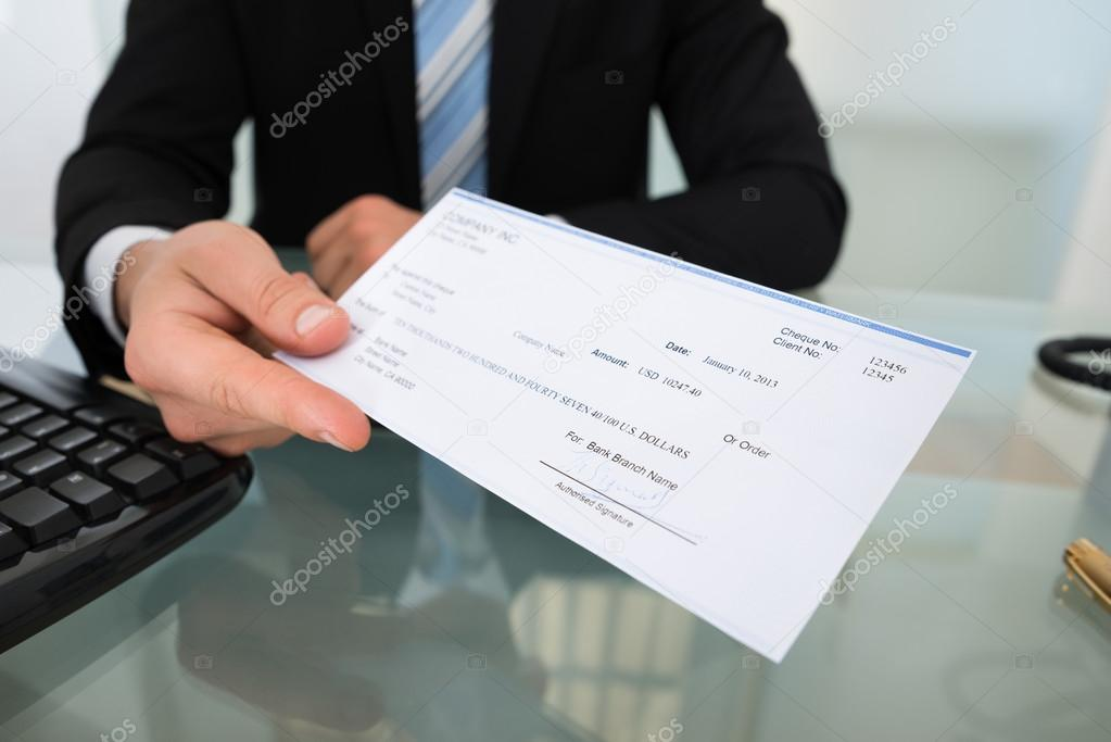 Midsection Of Businessman Giving Cheque