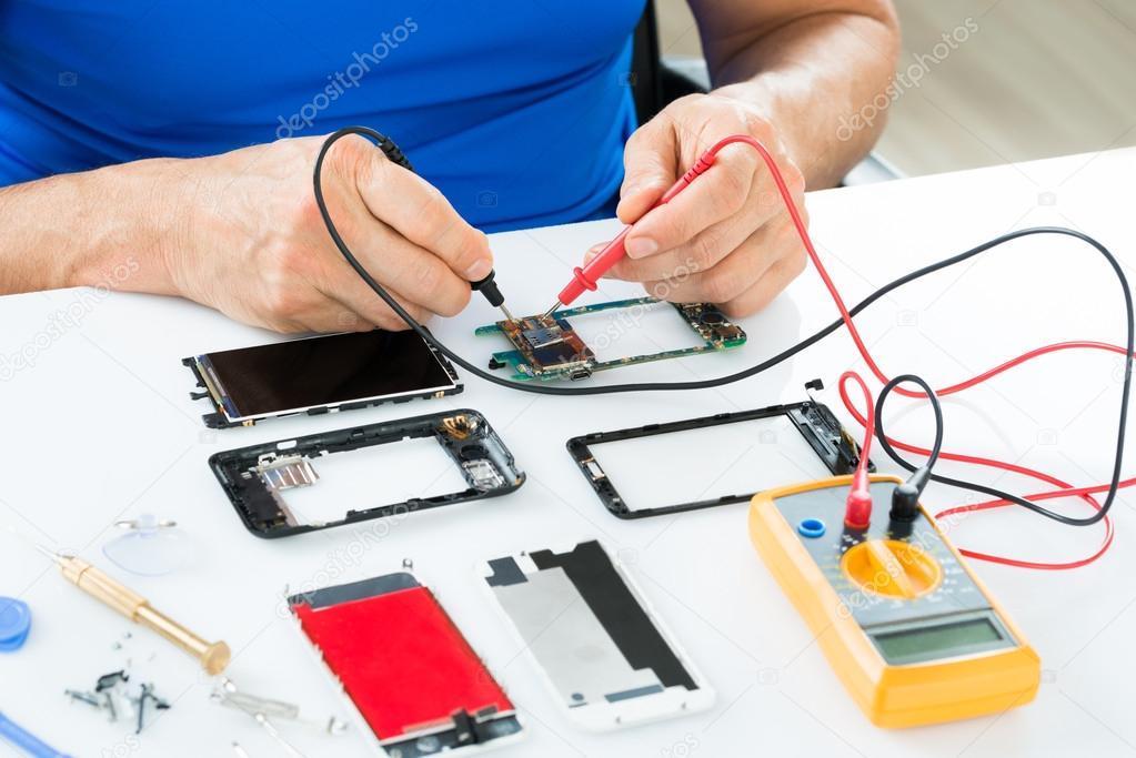 4df2248052e Close-up Of Man Repairing Cellphone With Multimeter - imágenes: reparacion  de celulares — Foto de AndreyPopov