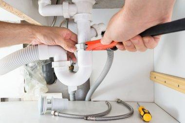 Male Plumber Fixing Sink