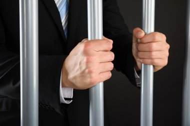 Businessman Holding Bars In Jail