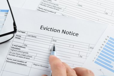 Hand With Pen Over Eviction Notice