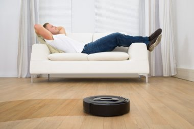 Man On Sofa with Robotic Vacuum Cleaner