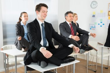 Meditating Businesspeople Sitting On Desks