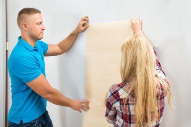 Couple Applying Wallpaper