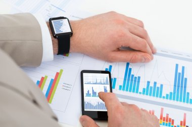 Close-up Of Businessman Analyzing Graph With Mobile Phone And Smartwatch stock vector