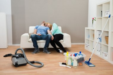 Exhausted Couple On Sofa In Living Room