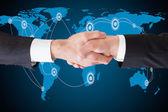 Podnikatelé, třesoucí se ruce proti mapa světa