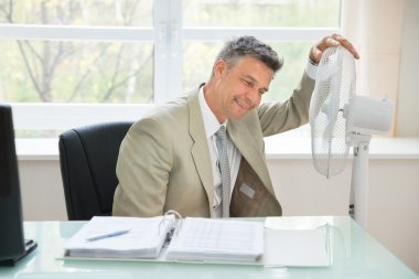 Businessman Sitting Near Fan