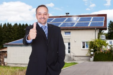 Businessman With Thumb Up In Front Of House