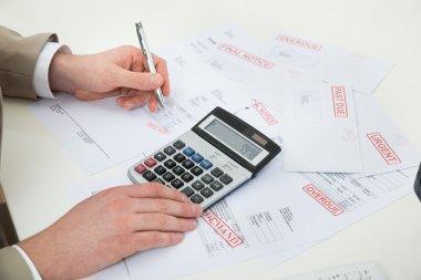 Businessman Calculating Unpaid Bills