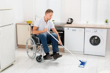 Man On Wheelchair Cleaning Floor