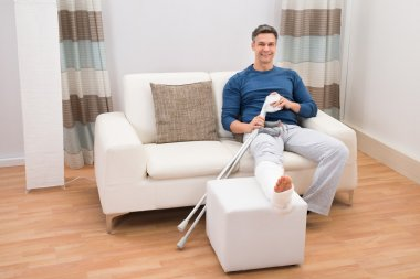 Man Sitting On Sofa With Crutches