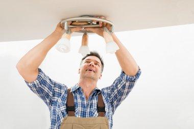 Technician Fixing Light